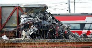 The wreckage of a high-speed train locomotive is crammed onto the wagon of another train after it derailed striking another train on adjacent tracks in the countryside near the town of Lodi, northern Italy, Thursday, Feb. 6, 2020. Italian authorities say a high-speed passenger train has derailed in northern Italy, killing two railway workers and injuring 27 people. (AP Photo/Antonio Calanni)